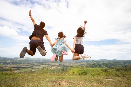 Happy active asian family jumping at the top of mountain