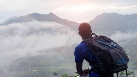 Excursionista hombre africano con mochila en la cima de la colina cubierta de niebla estilo 16: 9