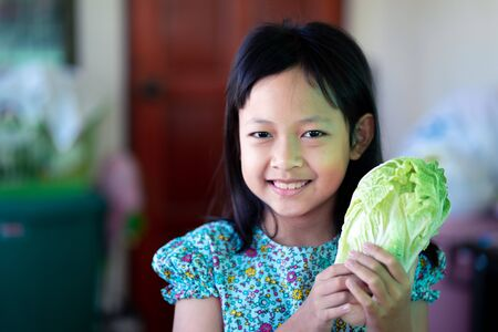 Smile asian child girl holding vegetables for cooking in the kitchen