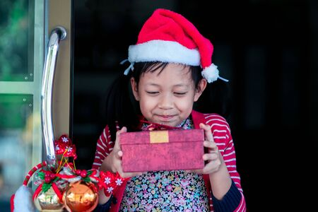 Asian smiling beautiful girl holding a gift box behind door at home.Christmas or X-mas concept