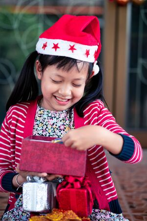 Cute girl received and open holiday gift with excited about her christmas box.