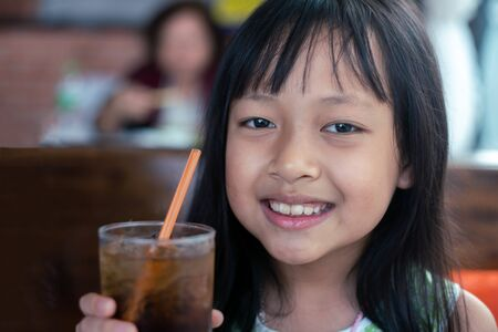 Asian children holding  and drinking cold drink in restaurant Unhealthy food and drink for Children concept.