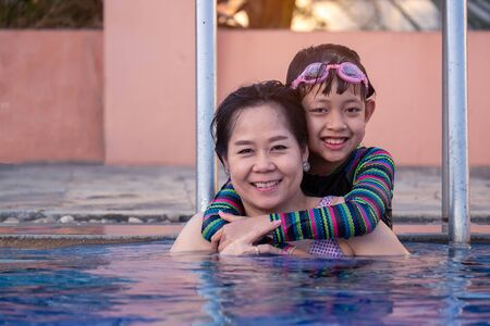 Mother and daughter hugging and playing in swimming pool