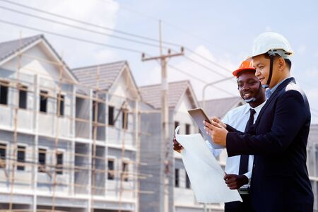 Asian and African architect engineer two expertise team plan with a building in background.