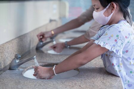 Child girl and mother washing hands with wear face mask in bathroom