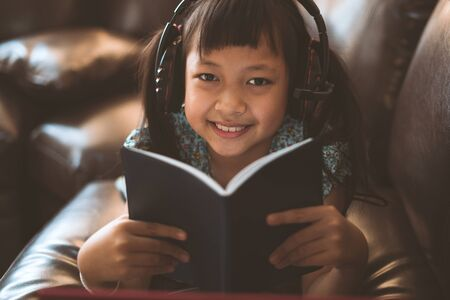 Happy little child girl lying on sofa with learning by  laptop and writing a book at home,Social distance during quarantine, Online education concept