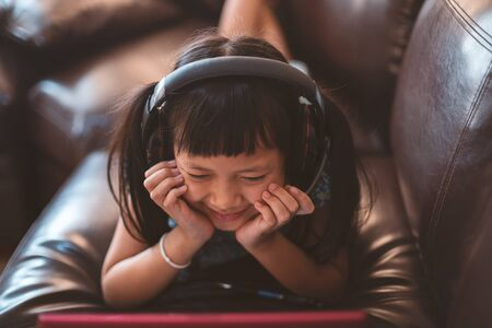 Happy little child girl lying on sofa with learning by  laptop at home,Social distance during quarantine, Online education concept Фото со стока