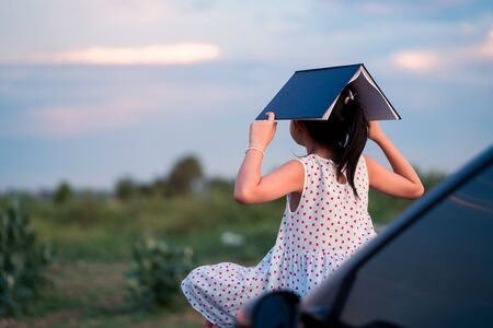 Little child girl  sitting and relaxing on a car reading a book in a green nature background