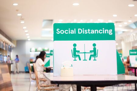 Social Distancing sign board stand on the table in food center of supermarket