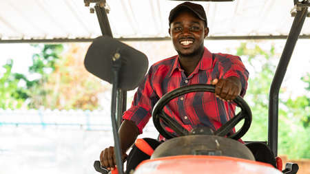 African farmer driving tractor in farm during harvest in countryside. Agriculture or cultivation concept