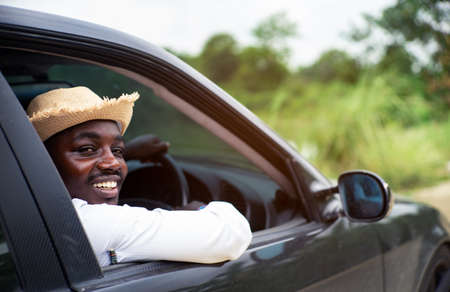 African man driver smiling while sitting in a car with open front window