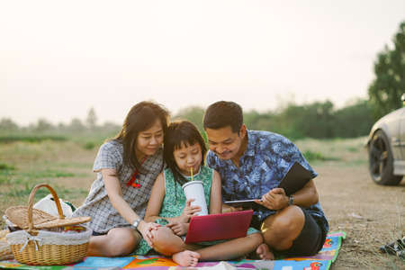 Happy family learning by laptop and having a picnic outdoor