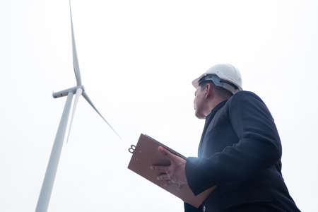Male engineer looking and writing plan on clipboard against wind turbine