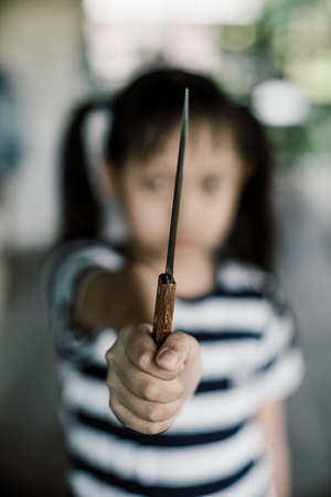 Angry little child girl with a knife in her hand
