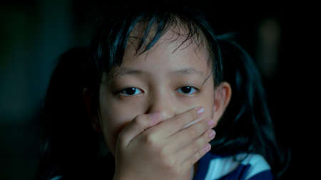 Sad little child girl covering her mouth with hands in dark room.16:9 style