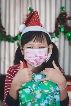 Asian little girl holding a gift box with wear face mask in christmas day