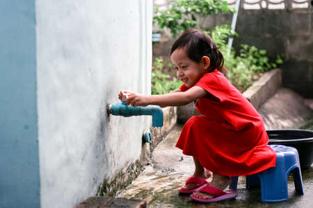 Asian little girl washing hands and close at home