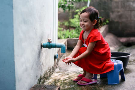 Asian little girl washing hands at home