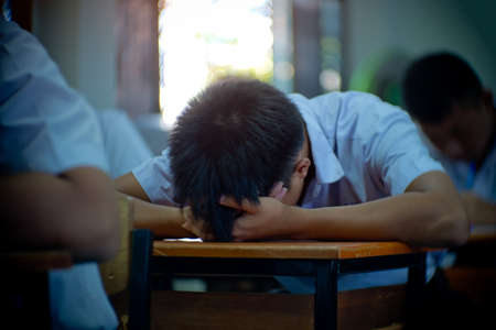 Students taking exam with stress in school classroom