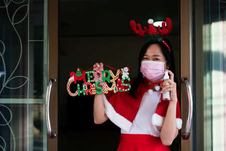 Woman in Santa Claus suit with wearing face mask and holding alcohol spray in christmas day