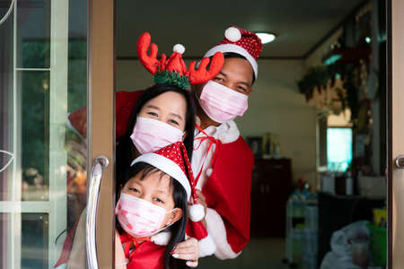 Happy asian family daughter mother and father wearing face mask in christmas day Stock fotó
