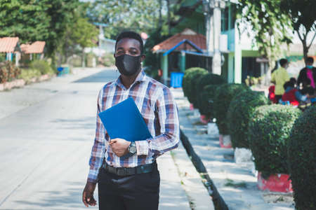 Portrait of cheerful african teacher in mask standing outdoor at school