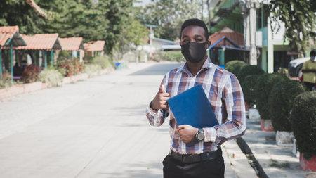Portrait of african teacher in face mask standing outdoor at school