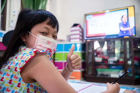 Little child girl learning on TV or smart phone at home with wearing face mask,Social distance during quarantine, Online education concept Stock fotó