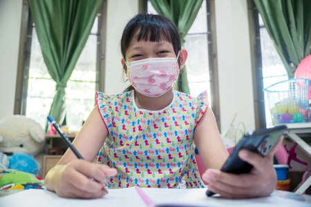 Little child girl learning on smart phone at home with wearing face mask,Social distance during quarantine, Online education concept