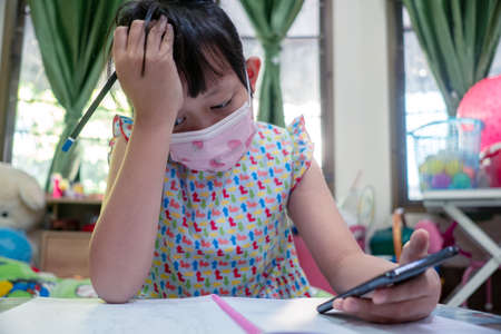 Serious little child girl learning on smart phone at home with wearing face mask,Social distance during quarantine, Online education concept