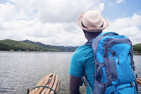African traveler man rafting in river with backpack Stock fotó
