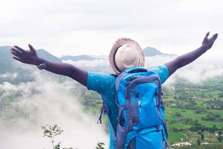 Freedom african  man traveler and hiker with backpack at the top of the hill covered with mist Stock fotó
