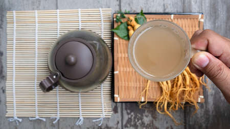 Hand holding a cup of ginseng tea,The concept of healthy drink