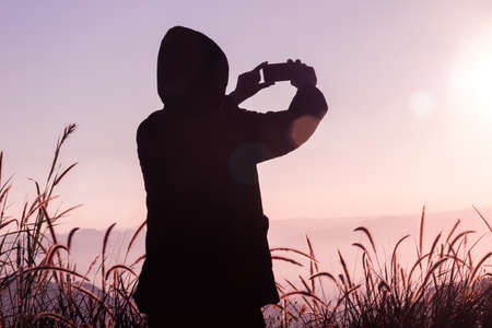 Traveler man wear sweater take pictures with a smartphone on top of the mountain