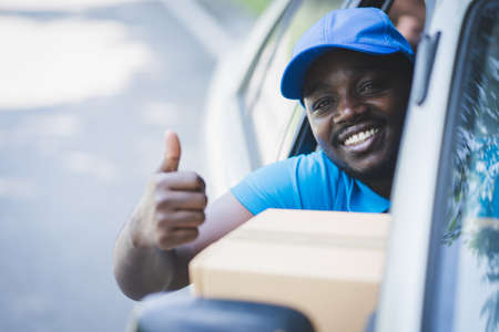 African postal delivery courier man delivering package in car