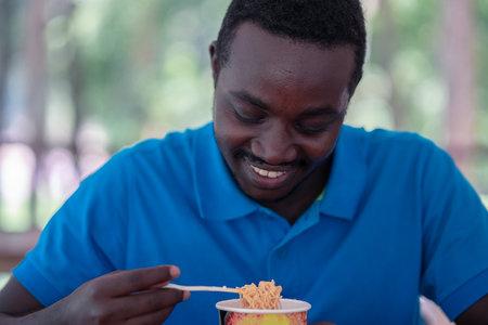 African man eating instant noodle soup Stock fotó