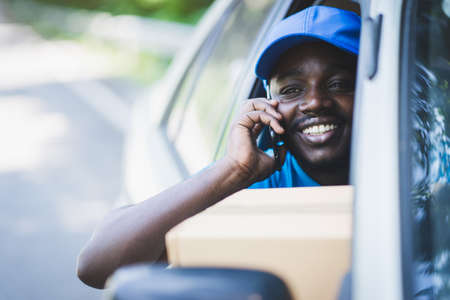 African postal delivery courier man using smart phone and delivering package in car