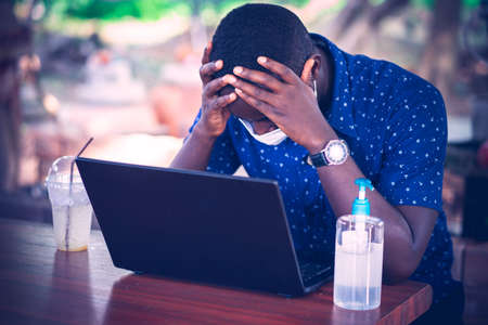 Serious african man wearing a mask and using a laptop at home . WHF or Work from home concept