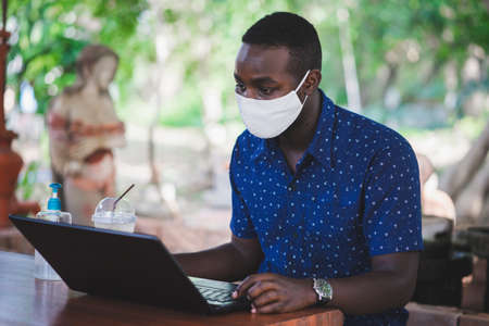African man wearing a mask and using a laptop at home . WHF or Work from home concept Stock fotó