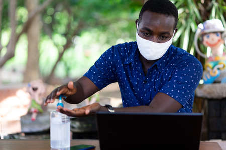 African man press sanitizer gel for washing hands for protection corona virus disease (COVID-19) during work from home Stock fotó