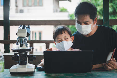 Smiling father and daughter wearing face mask and learning from home with laptop and microscope.Coronavirus or Covid-19 Outbreak school shutdowns Stock fotó