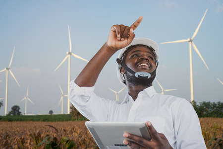 African engineer wearing white hard hat standing with digital tablet against wind turbine Stock fotó
