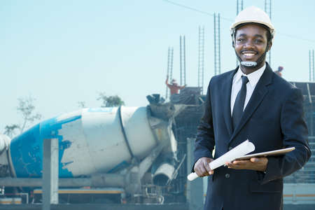 Portrait of African  site contractor engineer with hard hat holding blue print paper and tablet with building in background Stock fotó