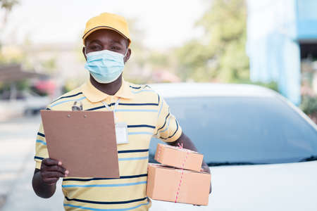 African delivery man holding boxs and cardboard with wearing face mask