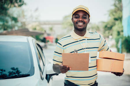 African male postal delivery courier man holding delivering package boxs and cardboard