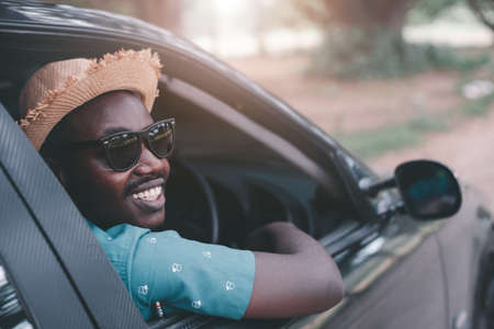 Happy african driver smiling while sitting in a car with open front window Stock Photo