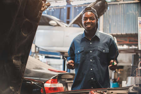 African maintenance male checking car, service via insurance system at garage