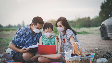 Happy family learning by laptop and having a picnic in outdoor with wearing face mask