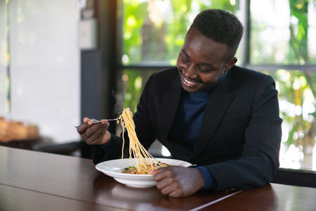 African businessman having a happy lunch with eating Spaghetti in restaurant