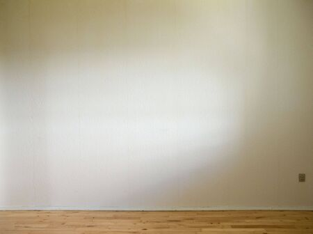 white wall with wooden floor and daylight from the side Stock Photo